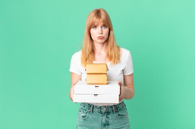 Ładna czerwona głowa kobieta trzymająca pudełka z fast foodami na wynos