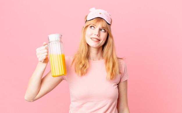 Ładna czerwona głowa kobieta ubrana w piżamę i trzymająca sok pomarańczowy. koncepcja zdrowego śniadania
