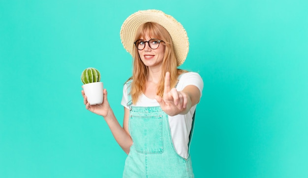 Ładna czerwona głowa kobieta uśmiecha się dumnie i pewnie robi numer jeden i trzyma doniczkowy kaktus. koncepcja rolnika
