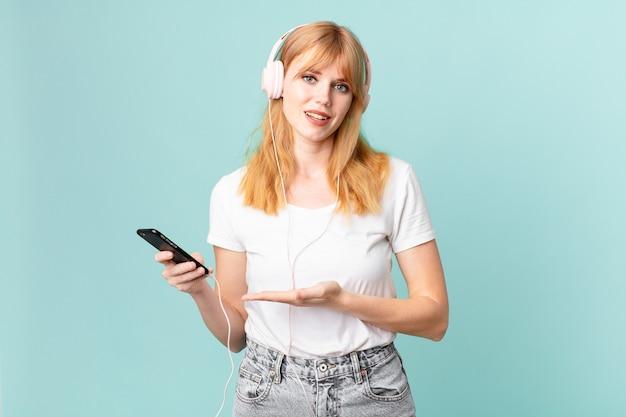 Ładna czerwona głowa kobieta uśmiecha się radośnie, czuje się szczęśliwa i pokazuje koncepcję oraz słucha muzyki przez słuchawki