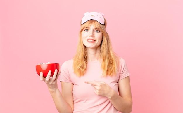 Ładna czerwona głowa kobieta uśmiecha się radośnie, czuje się szczęśliwa i wskazuje na bok, ubrana w piżamę i trzymająca miskę z płatkami