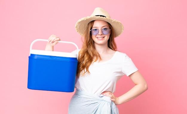 Ładna czerwona głowa kobieta uśmiecha się radośnie z ręką na biodrze i pewnie trzyma piknikową przenośną lodówkę