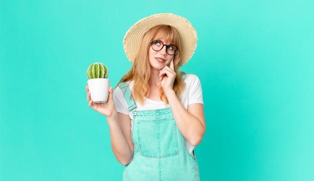 Ładna czerwona głowa kobieta uśmiecha się szczęśliwie i marzy lub wątpi i trzyma doniczkowy kaktus. koncepcja rolnika