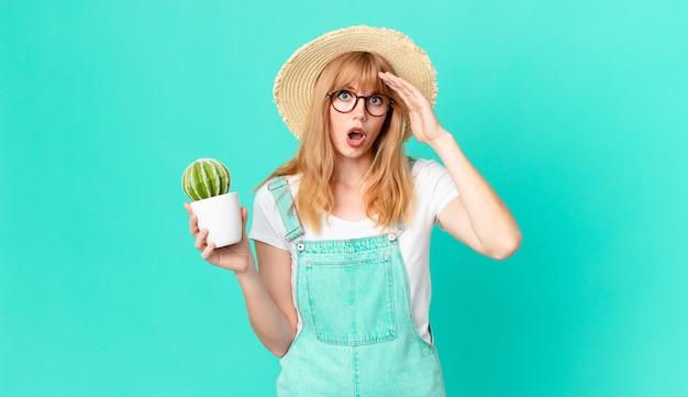 Ładna czerwona głowa kobieta wygląda na szczęśliwą, zdumioną i zdziwioną i trzyma kaktus w doniczce. koncepcja rolnika