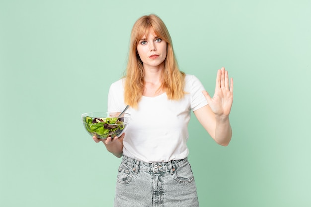Ładna czerwona głowa kobieta wygląda poważnie pokazując otwartą dłoń, co gest stop i trzymając sałatkę. koncepcja diety