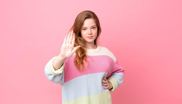 Ładna czerwona głowa kobieta wygląda poważnie pokazując otwartą dłoń, wykonując gest zatrzymania