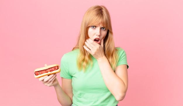 Ładna czerwona głowa kobieta z szeroko otwartymi ustami i oczami, ręką na brodzie i trzymającą hot doga