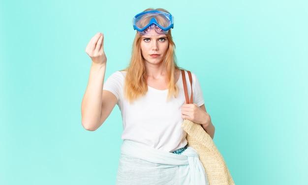 Ładna czerwona głowa kobiety robiąca gest kaprysu lub pieniędzy, mówiąca, że musisz zapłacić goglami. koncepcja lato