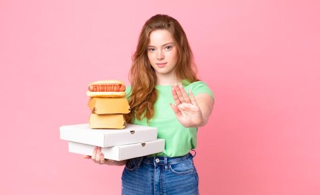 Ładna czerwona głowa kobiety trzymającej pudełka z fast foodami na wynos