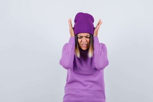 Ładna dama z rękami na uszach w swetrze, czapce i wyglądająca na zirytowaną. przedni widok.