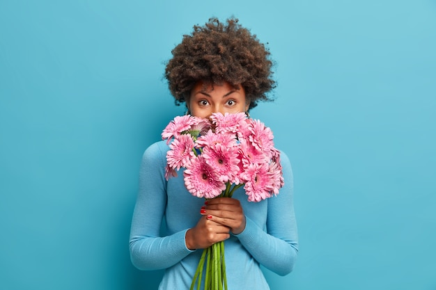 Ładna, delikatna afroamerykanka pachnie różowymi kwiatami gerbera, cieszy się przyjemnym zapachem, trzyma bukiet w dłoniach