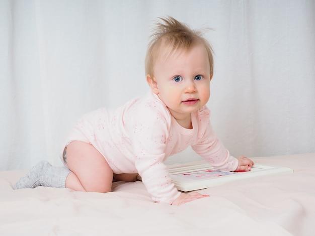 Ładna, delikatna dziewczynka, 10 miesięcy, czołganie się, patrząc zdziwiona w kamerę, zbliżenie. portret dziewczynki w odcieniach różu. koncepcja produktów dla dzieci. prawdziwe dziecięce emocje.