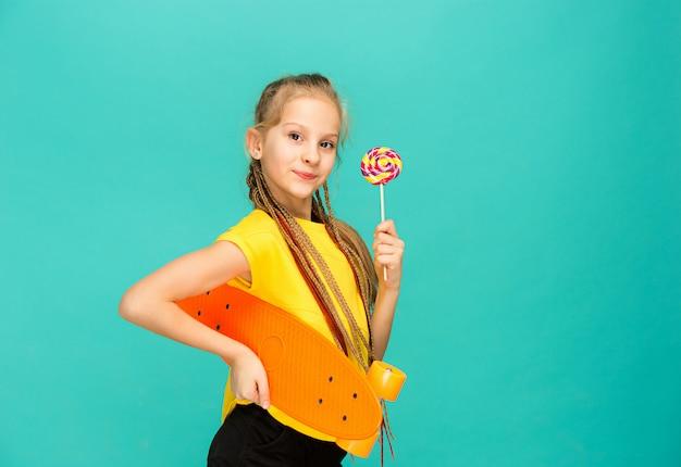 Ładna deskorolka dziewczyna trzyma deskorolka