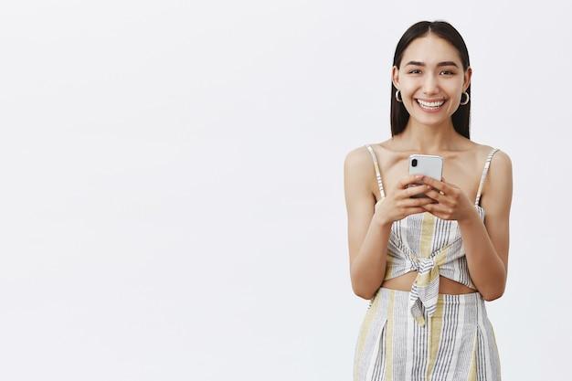 Ładna, diabelska i wesoła ciemnowłosa suczka z pieprzykiem pod wargą, uśmiechająca się radośnie, patrząc i trzymając smartfon, sprawdzając nową aplikację.