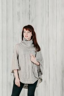 Ładna, długowłosa dziewczyna w szarym swetrze, uśmiechnięta, jasne tło