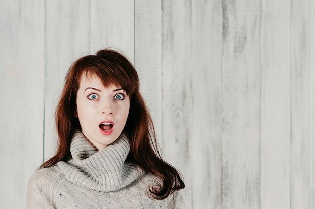 Ładna długowłosa dziewczyna w szarym swetrze, zaskoczone duże oczy, otwarte usta