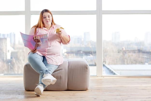Ładna, dobrze wyglądająca kobieta je smaczną przekąskę podczas czytania magazynu o modzie