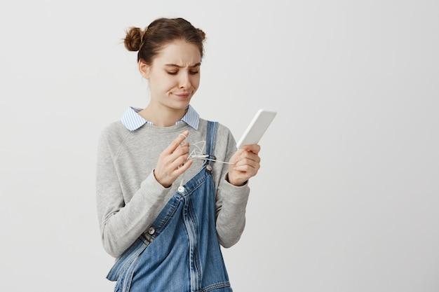 Ładna, dorosła dziewczyna denerwuje się, próbując rozplątać przewód ze słuchawek. kobieta w dorywczo gospodarstwa smartphone z rozwikłać słuchawki jest zdenerwowany. ludzkie reakcje