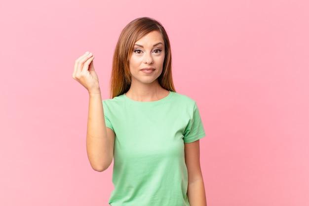 Ładna dorosła kobieta robi gest kaprysu lub pieniędzy, każąc ci zapłacić