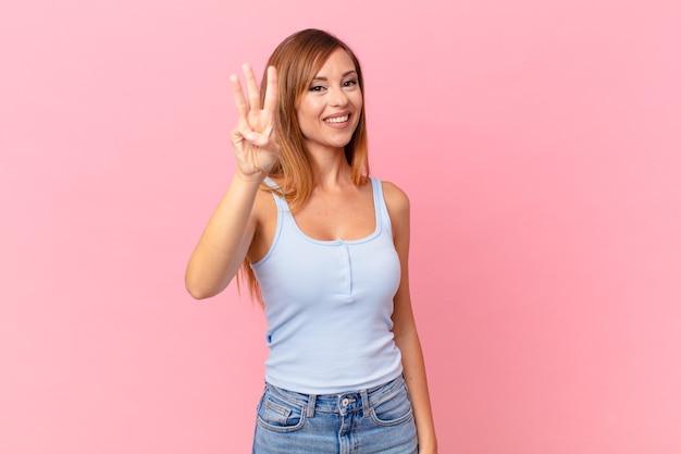 Ładna dorosła kobieta uśmiechnięta i wyglądająca przyjaźnie, pokazująca numer trzy