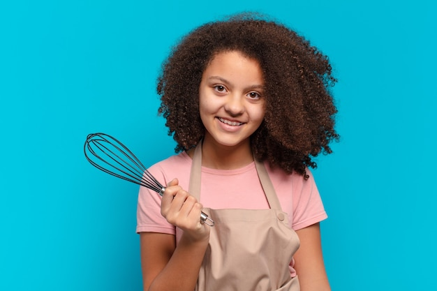 Ładna dziewczyna afro nastolatek gotowanie z fartuchem i mikserem. koncepcja piekarza
