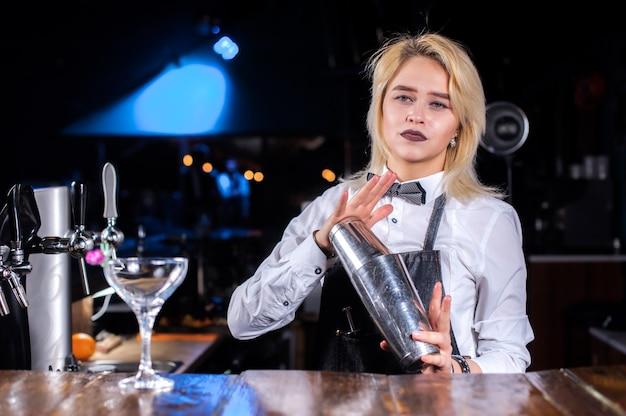 Ładna dziewczyna barman wlewając świeży napój alkoholowy do szklanek w koktajl barach