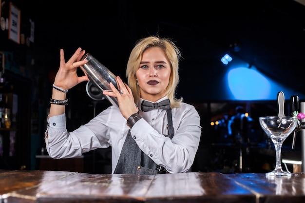 Ładna dziewczyna barmanka robi show tworząc koktajl