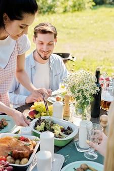 Ładna dziewczyna biorąc sałatkę wegetariańską z pojemnika, aby położyć ją na talerzu, stojąc przy stole serwowanym ze swoim chłopakiem w pobliżu