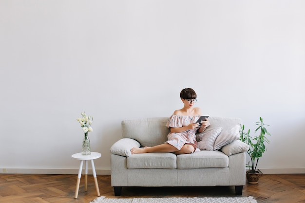 Ładna dziewczyna boso w okularach leży na kanapie z nowym gadżetem, ciesząc się weekendem