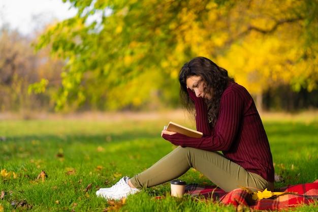 Ładna dziewczyna czyta książkę i pije kawę na zielonym trawniku w jesiennym parku. jesienny nastrój. przytulne miejsce na samotność.