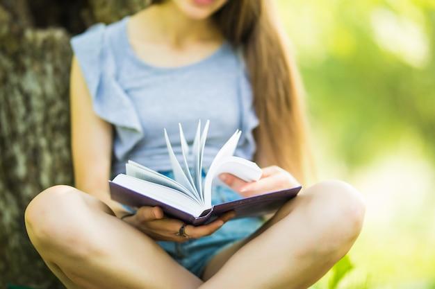 Ładna dziewczyna, czytanie książki w parku. student przygotowuje się do egzaminu. literacki wypoczynek na świeżym powietrzu.