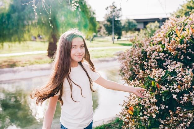 Ładna dziewczyna dotyka kwiaty w pobliżu jeziora w parku