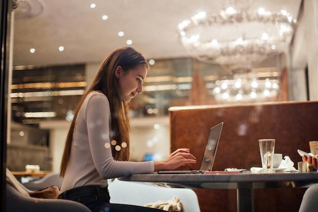 Ładna dziewczyna działa na laptopie w kawiarni hipster