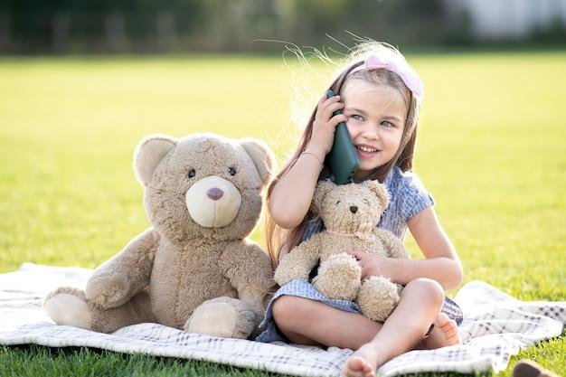 Ładna dziewczyna dziecko siedzi w letnim parku na zielonej trawie wraz z zabawką pluszowego misia rozmawia przez telefon komórkowy uśmiecha się szczęśliwie na zewnątrz w lecie.