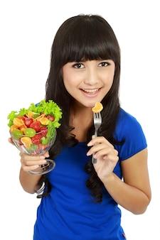 Ładna dziewczyna je owocowej sałatki, zdrowego świeżego śniadania, diety i opieki zdrowotnej pojęciem ,.