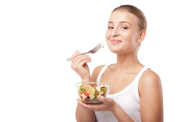 Ładna dziewczyna jedząca sałatkę owocową na białym tle