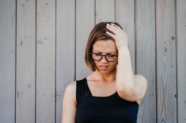 Ładna dziewczyna jest ubranym przypadkową koszulkę stoi nad drewnianym tłem cierpiącym z bólem głowy desperackim i stresującym się z powodu bólu i migreny. ręce na głowie.