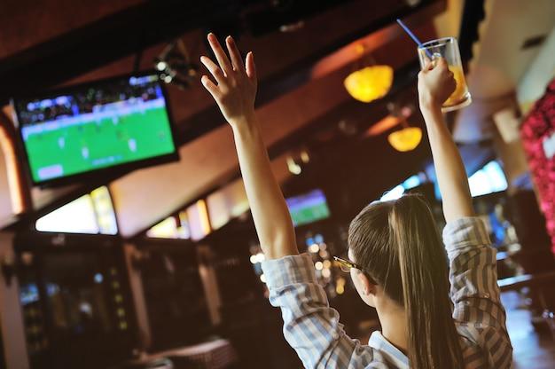 Ładna dziewczyna kibica z kuflem piwa w rękach ogląda piłkę nożną w barze sportowym