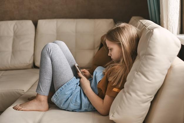 Ładna dziewczyna komunikuje się ze swoimi przyjaciółmi za pośrednictwem komunikatora podczas kwarantanny.