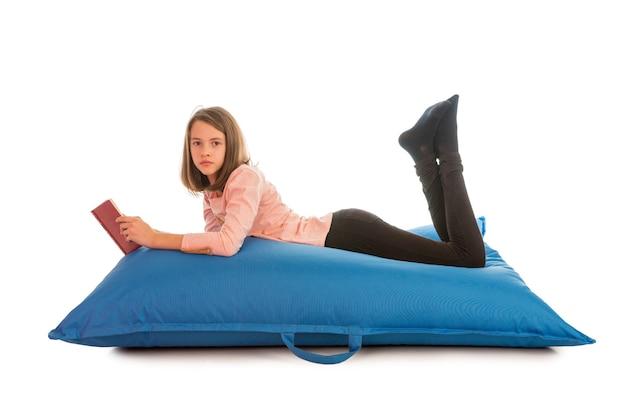 Ładna dziewczyna leżąc na niebieskiej kanapie beanbag w salonie lub innym pokoju i czytając książkę na białym tle