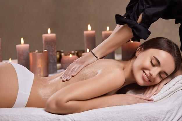 Ładna dziewczyna leżąca z nagimi plecami i po zabiegu na ciało masażem i kremem