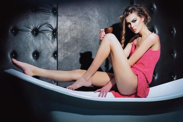 Ładna dziewczyna lub seksowna kobieta ze stylowym makijażem i długimi kręconymi włosami na sobie różową sukienkę w kropki pije kawę z kubka w białej wannie na czarnym skórzanym tle