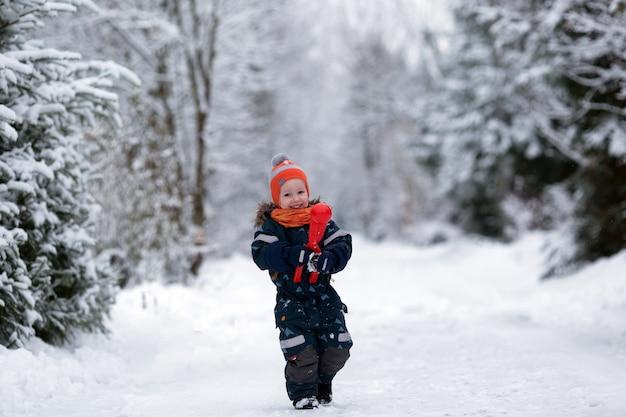 Ładna dziewczyna malucha na sobie zimowe ubrania zabawy na zewnątrz w śnieżny dzień. dziewczyna robi śnieżki. skopiuj miejsce