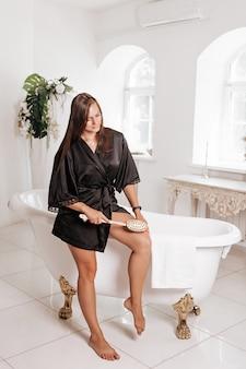 Ładna dziewczyna masuje skórę nóg szczoteczką do masażu na sucho. piękna kobieta masuje skórę nóg szczoteczką na sucho