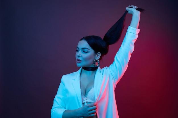 Ładna dziewczyna model nosić białą kurtkę trzymać kucyk stojak na tle studio kolorów. światło neonowe.