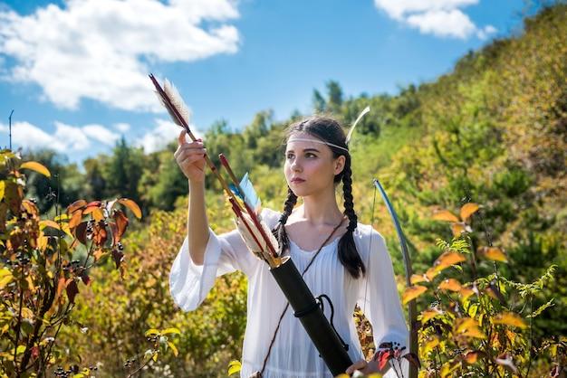 Ładna dziewczyna myśliwska strzelająca z łuku i strzał na łące
