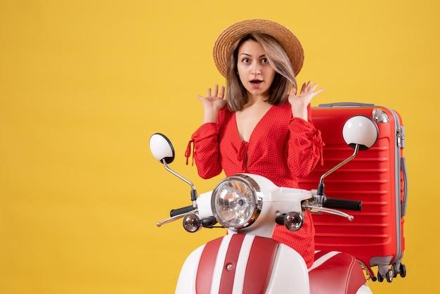 Ładna dziewczyna na motorowerze z czerwoną walizką myląca