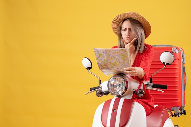 Ładna dziewczyna na motorowerze z czerwoną walizką patrząca na mapę