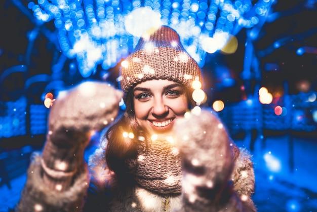 Ładna dziewczyna na ulicy z bożonarodzeniowe światła wokół