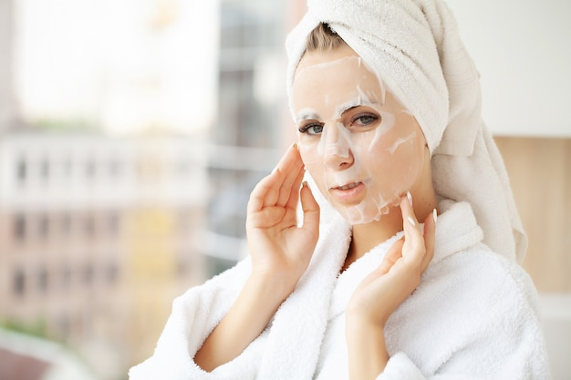 Ładna dziewczyna nosi maskę do pielęgnacji twarzy w domu.